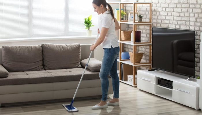 homeguide-apartment-cleaning-happy-young-maid-mopping